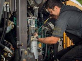 Serwisant sprawdza poziom oleju w maszynie budowlanej